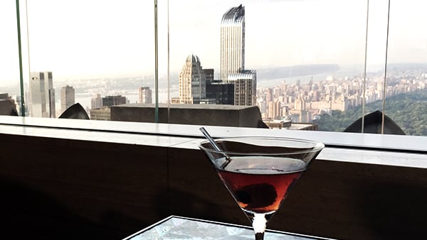 Martini on table of roof top bar overlooking New York