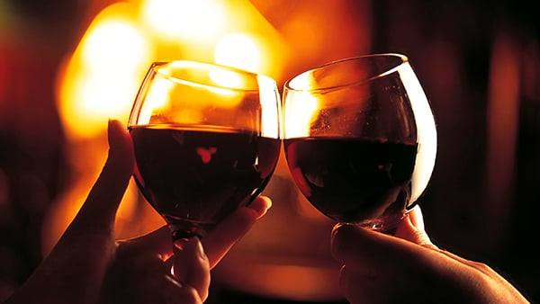 Two wine glasses cheersing in front of fire