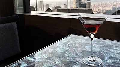 Martini on roof top bar table overlooking New York