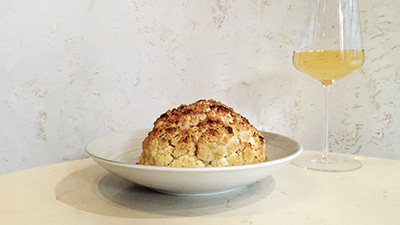Whole roasted cauliflower and glass of white wine