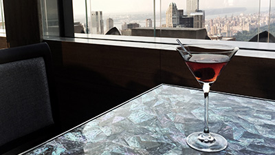 Martini on table of rooftop bar overlooking New York
